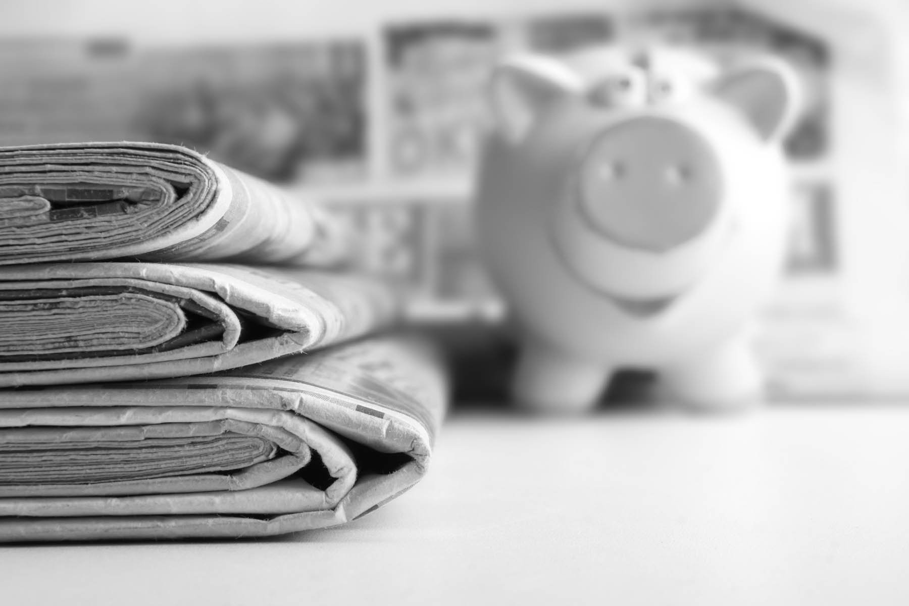 Stack of newspapers and piggy bank